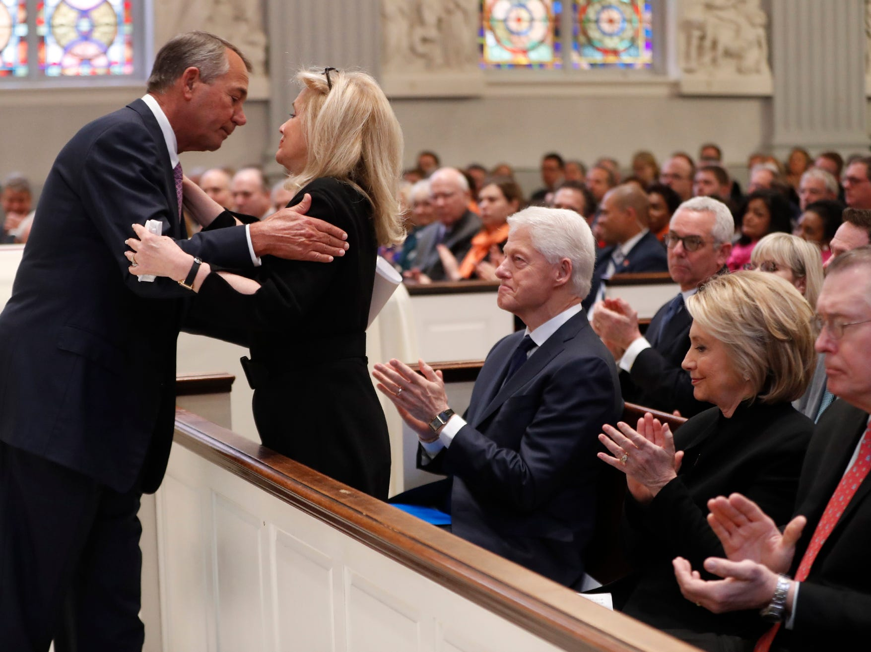Former House Speaker John Boehner hugs Rep. Debbie Dingell, D-Dearborn, during the funeral for her husband, former Rep. John Dingell, Thursday, Feb. 14, 2019 at Holy Trinity Catholic Church in Washington. Dingell, who represented southeast Michigan for 59 years in the House of Representatives, died last week at age 92. Seated are former President Bill Clinton and former Secretary of State Hillary Clinton.
