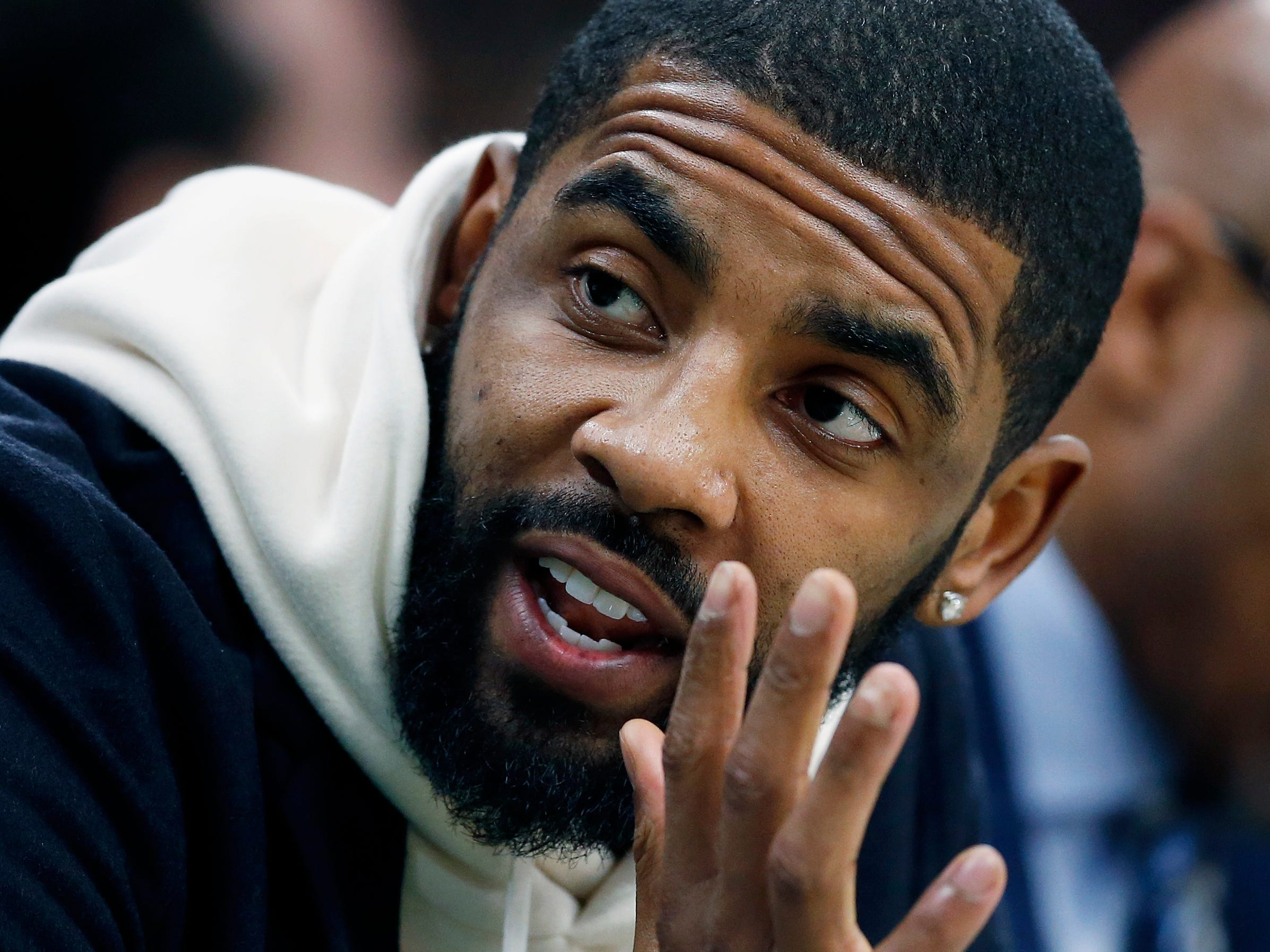 Boston Celtics' Kyrie Irving, who did not play, sits on the bench during the first half.