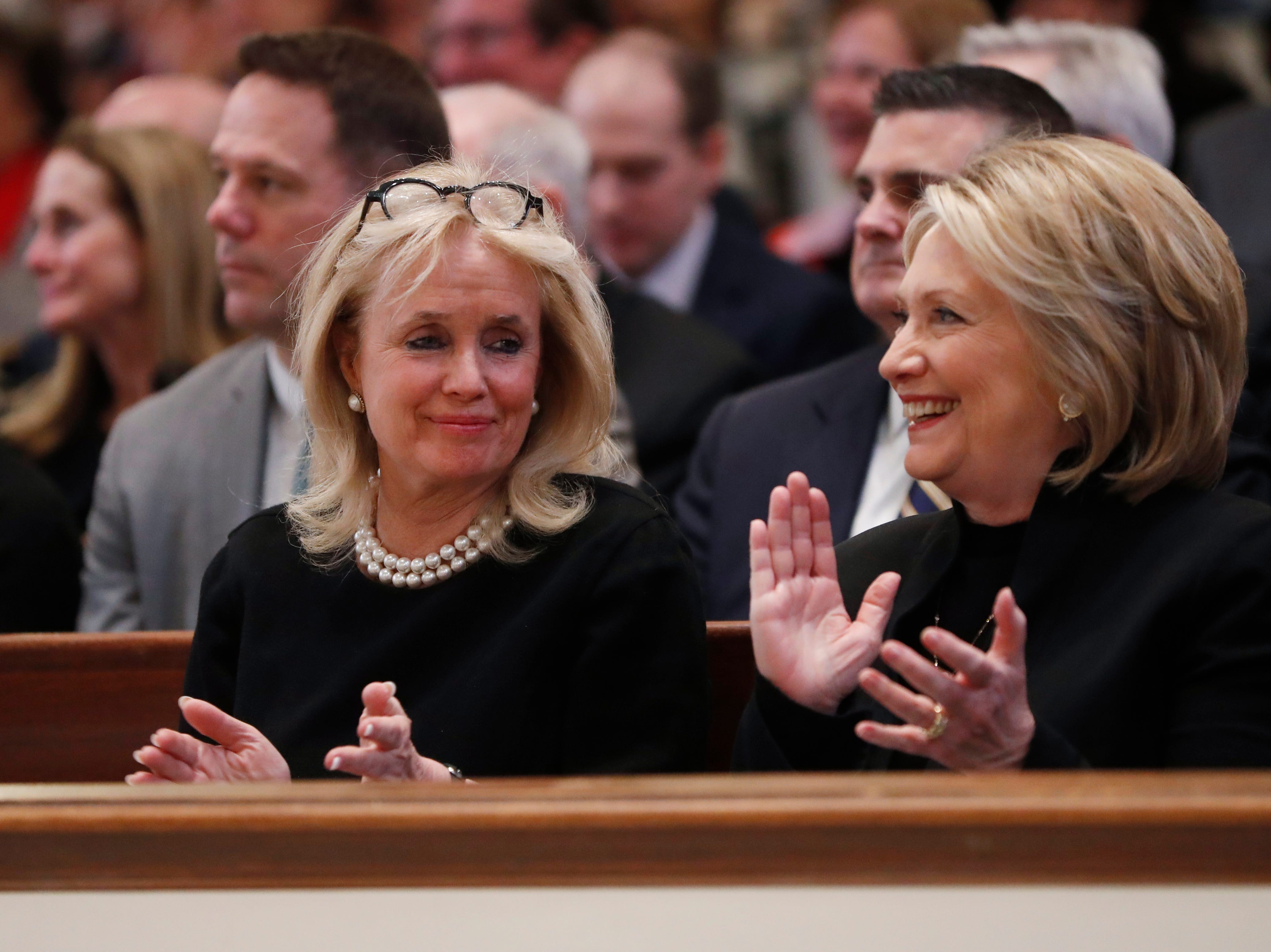 Rep. Debbie Dingell, D-Dearborn, left, talks with former Secretary of State Hillary Clinton, during the service for her husband, former Rep. John Dingell.