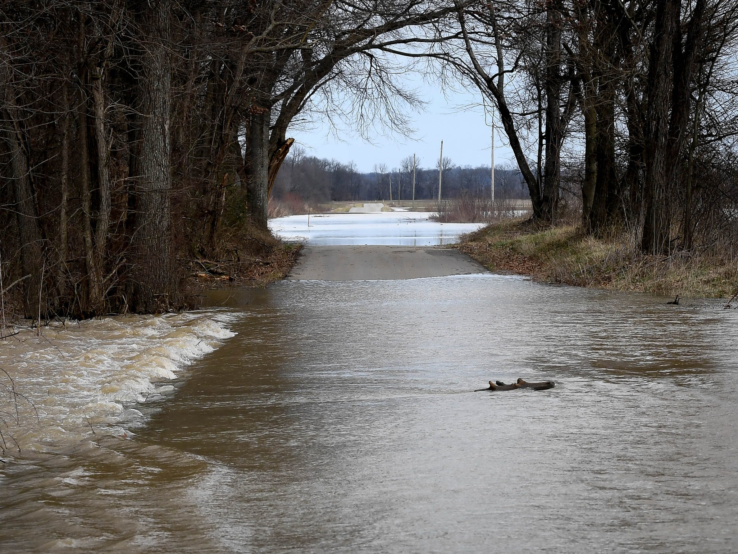 Flowing flood waters cover McDonald Landing Road in Henderson County Thursday, February 14, 2019.