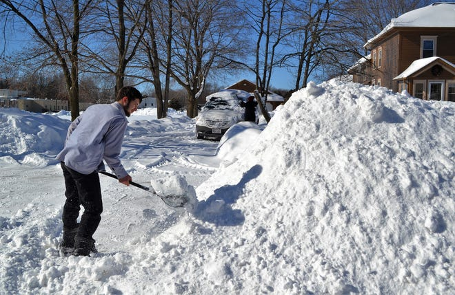 """Anthony Petrick of Oconto shovels snow in the driveway at his residence on Park Avenue on Wednesday, Feb. 12, as his sister Alicia Petrick sweeps snow off a van in the driveway. Even though it was only about 20 degrees, Anthony said he didn't wear a coat because """"it gets pretty hot when you shovel for a while."""""""