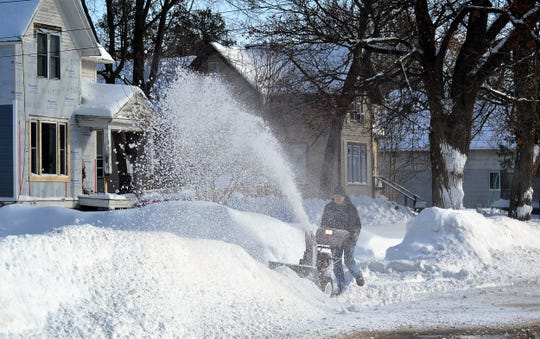 A man blows snow from a driveway on Madison Street in Oconto on Wednesday, Feb. 13. Much of the area received 12 inches of snow Tuesday.