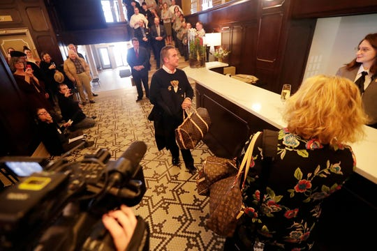 Green Bay Mayor Jim Schmitt checks in at the front desk at the Hotel Northland after a ceremony for its official opening on Thursday in downtown Green Bay.