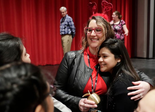 Marisol Evans, an English learner instructional coach at Washington Middle School is congratulated by her students after being presented with a Golden Apple award on Thursday.