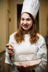 Clara Lawrence, 13, holds a bowl and whisk as she poses for a portrait on Thursday, Feb. 14, 2019. Lawrence is one three young chefs that will be participating in the upcoming CHOP! Cancer cook-off.
