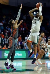 Miami guard Zach Johnson (5) makes the game winning basket over Clemson guard Shelton Mitchell (4) Wednesday night in Coral Gables, Fla.