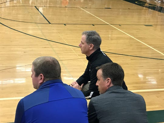 Great Falls Central Catholic boys' basketball coach Eric Vincent, kneeling in front of assistants Jerry Jordan and Tyler Sealey, directs the Mustangs to victory Thursday afternoon at CMR Fieldhouse.