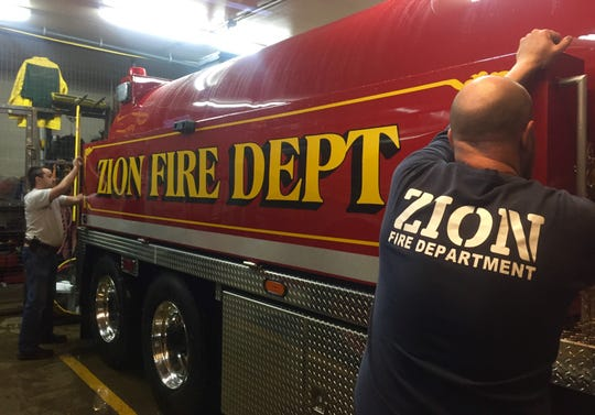 "Melvin Fulkerson, left, and Chad Patterson close up the ""dump tank"" on the side of the Zion Volunteer Fire Department's new tanker truck."