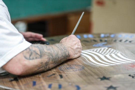 An inmate works on a large wooden seal for American Legion George D. Vickery Post #608, located inside of the Pendleton Correctional Facility in Ind., on Wednesday, Feb. 6, 2019.