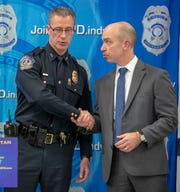 IMPD Bryan Roach (left), and Grant Mendenhall, FBI Special Agent in Charge of Indianapolis, shake hands after an announcement about a multi-agency operation that resulted in 25 people charged, plus removal of guns and narcotics from Indianapolis, Thursday, Feb. 14, 2019. The operation, dubbed Garage Band, resulted in the seizing of methamphetamine, heroin, and cocaine, plus 40 firearms of varying types.