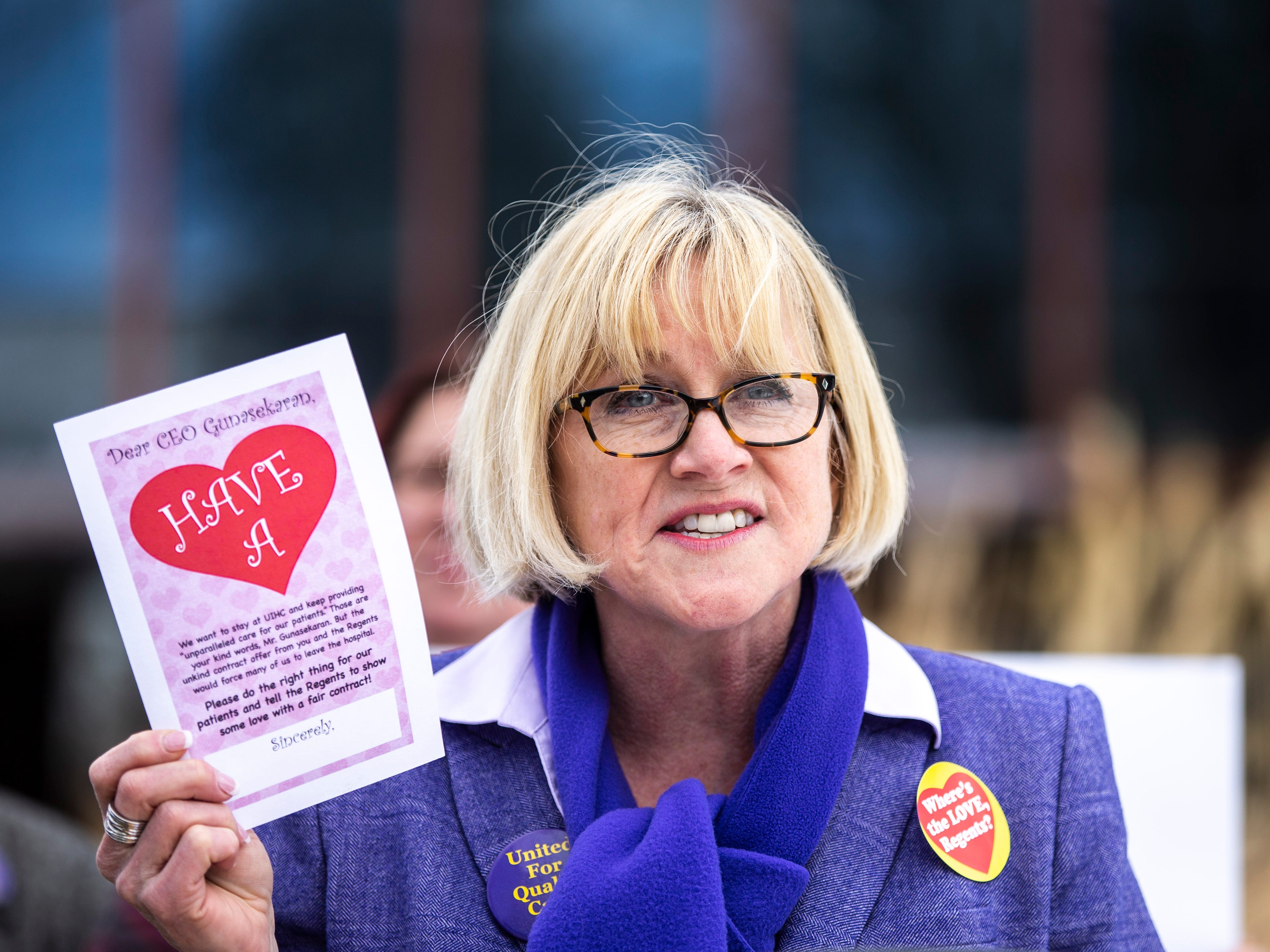 Cathy Glasson, SEIU Local 199 president, holds up a card while speaking at a press conference with members of the UIHC union during a Valentine's Day protest over bargaining with the hospital CEO and Regents, Thursday, Feb. 14, 2019 at the University of Iowa Hospitals and Clinics in Iowa City, Iowa.
