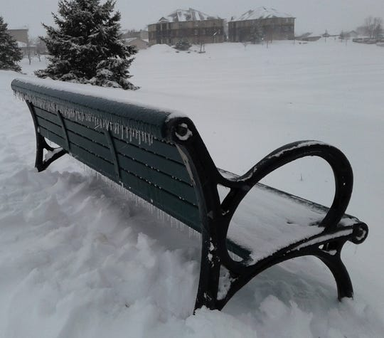 A desolate bench gathers snow at Liberty Centre park in North Liberty during the blizzard Wednesday of this week.