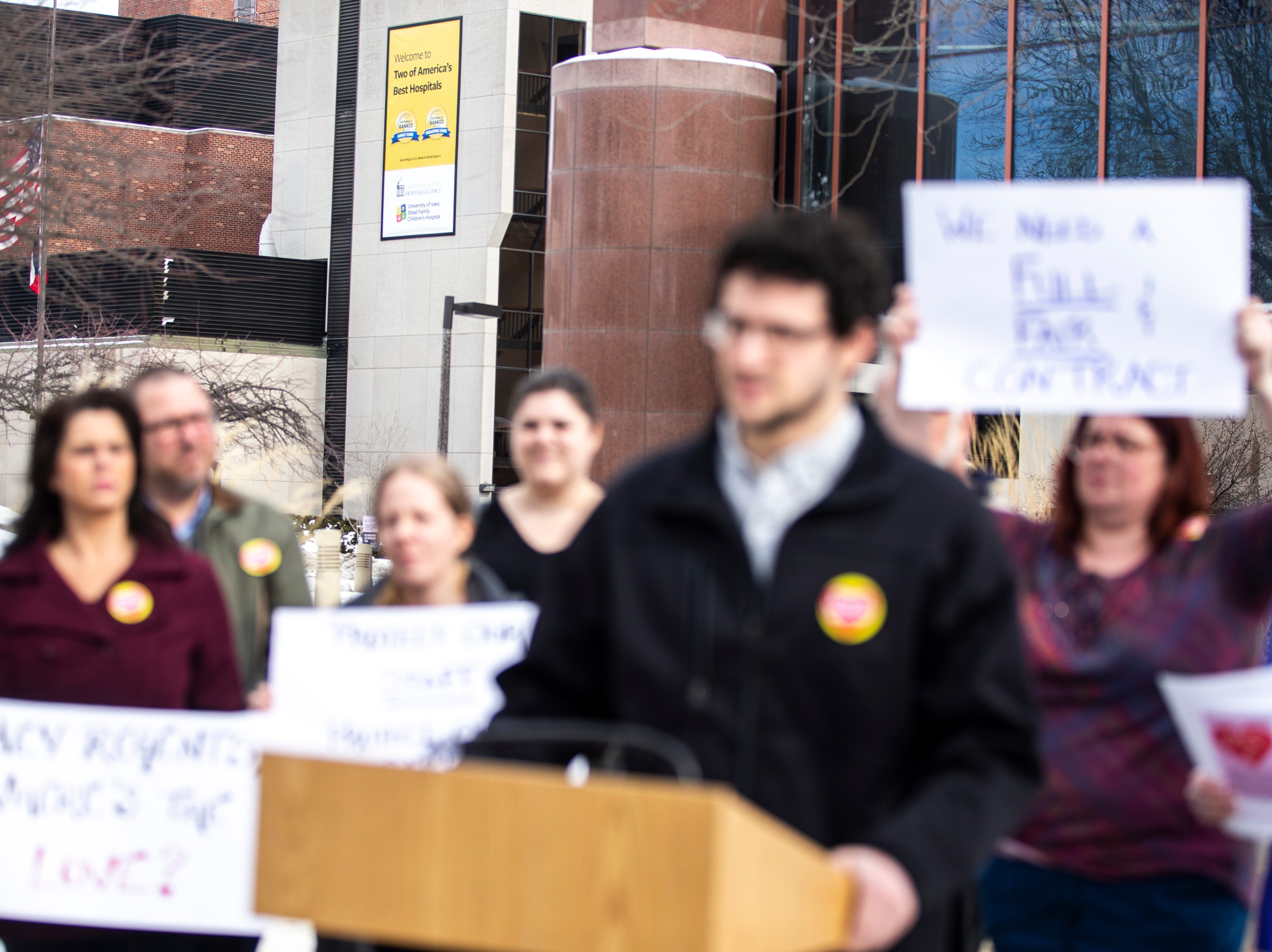 """UIHC union members hold up signs in front of the hospital that reads, """"Two of America's Best Hospitals"""" while Coen Olson, a medical lab scientist, speaks at a press conference during a Valentine's Day protest over bargaining with the hospital CEO and Regents, Thursday, Feb. 14, 2019 at the University of Iowa Hospitals and Clinics in Iowa City, Iowa."""