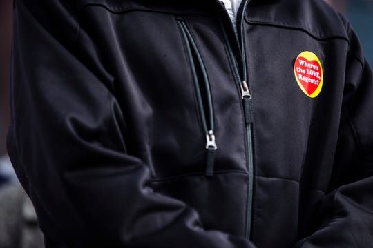 """A person wearing a sticker reading """"Where's the LOVE Regents?"""" stands at a press conference with members of the UIHC union during a Valentine's Day protest over bargaining with the hospital CEO and Regents, Thursday, Feb. 14, 2019 at the University of Iowa Hospitals and Clinics in Iowa City, Iowa."""