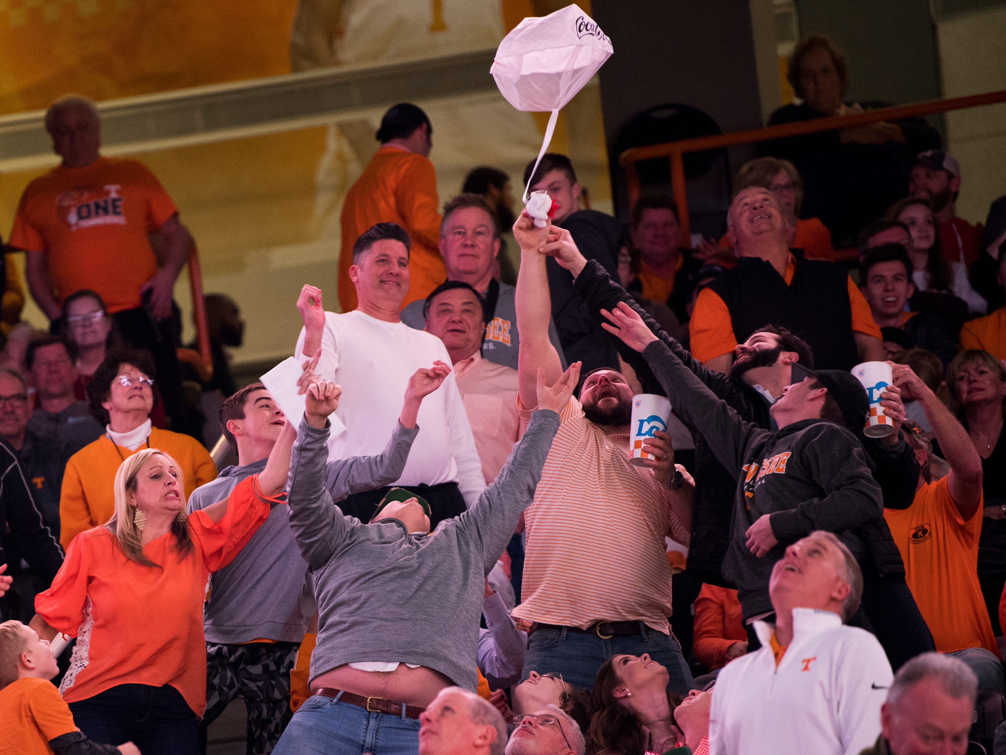 Fans reach for a parachuting plush bear during Tennessee's home SEC game against South Carolina at Thompson-Boling Arena in Knoxville on Wednesday, February 13, 2019.