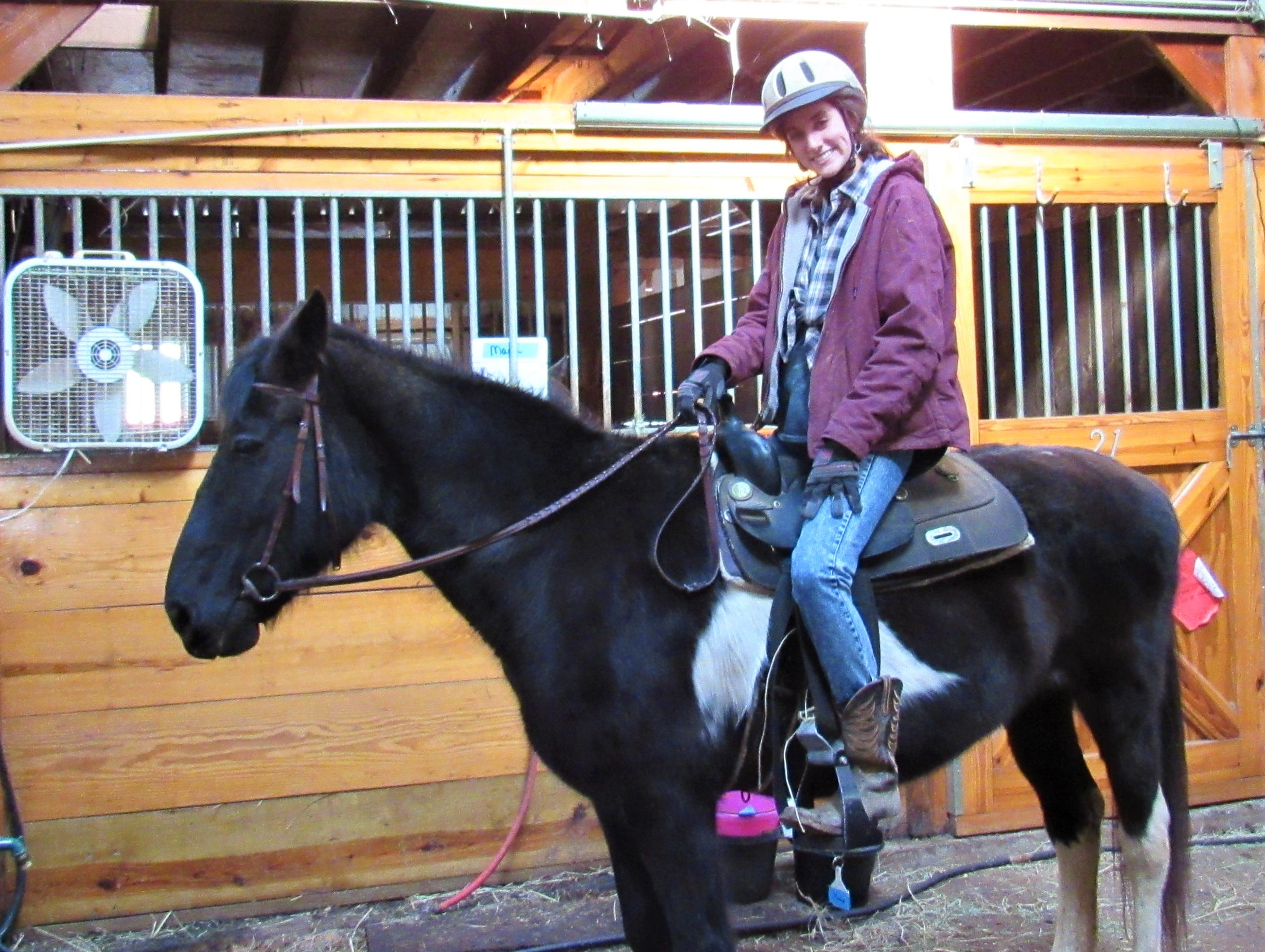 Volunteer exercise rider Victoria Miller gets ready to take Blitzen through a strength-building workout.