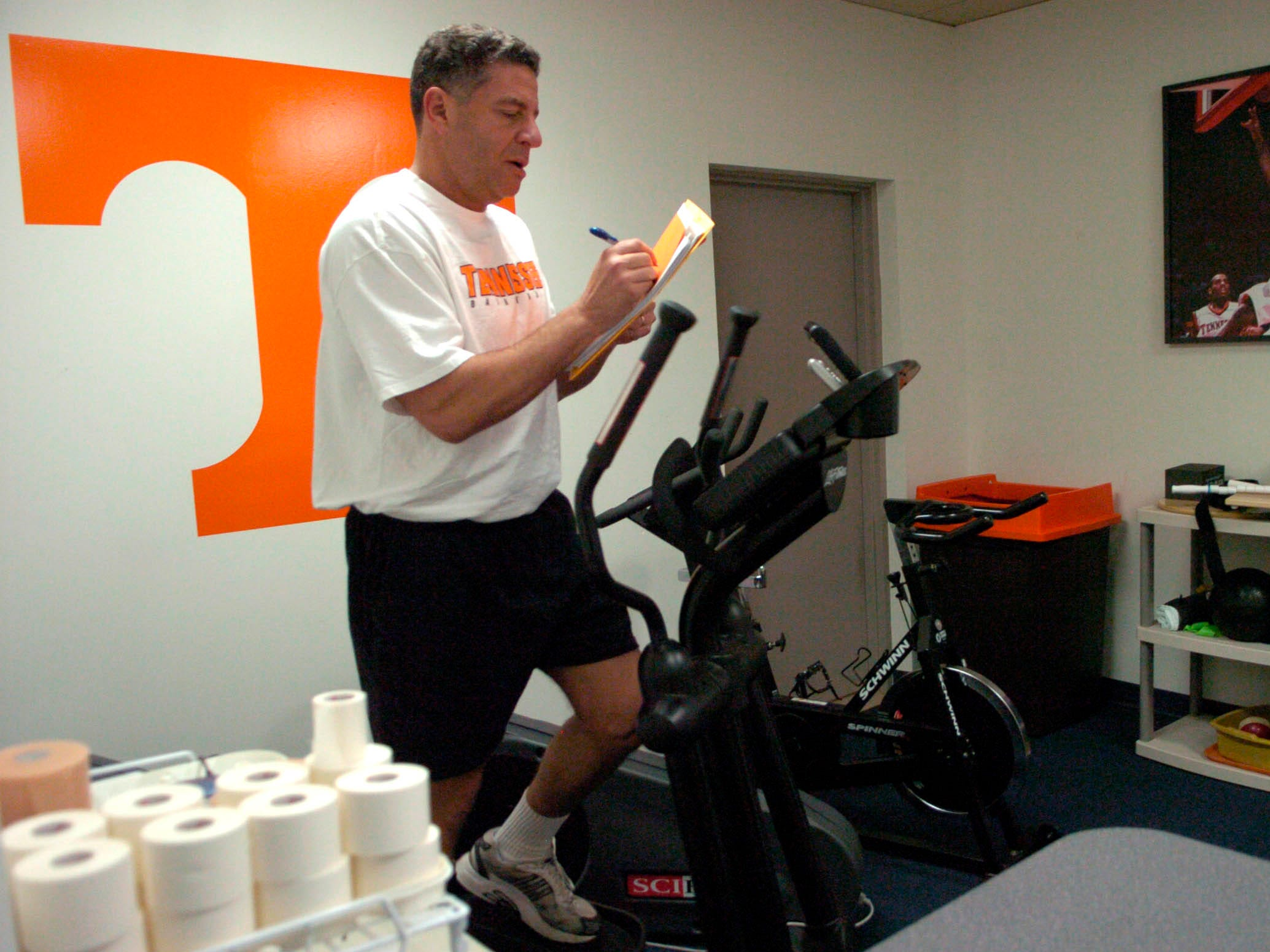 As he works out in the training room, Tennessee basketball coach Bruce Pearl takes notes while watching tape of an Auburn basketball game. 2006