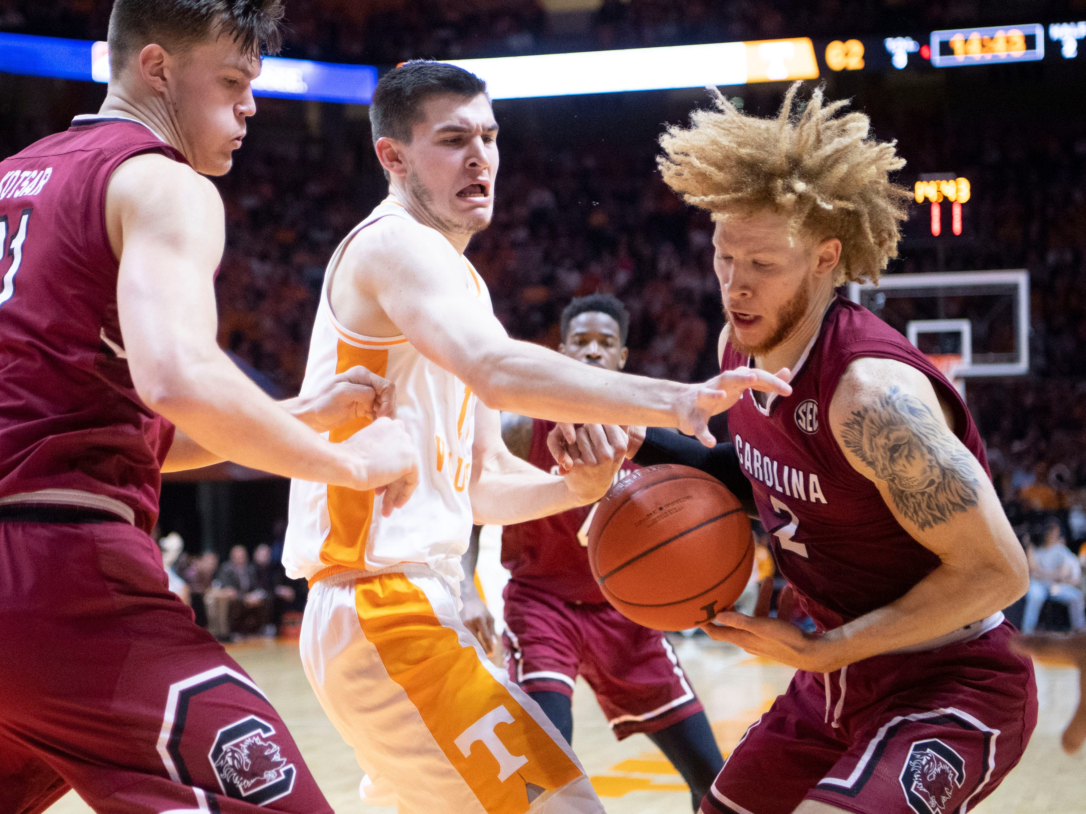 South Carolina's Mark Kotsar (21) and Hassani Gravett (2) battle for the loose ball with Tennessee's John Fulkerson (10) on Wednesday, February 13, 2019.