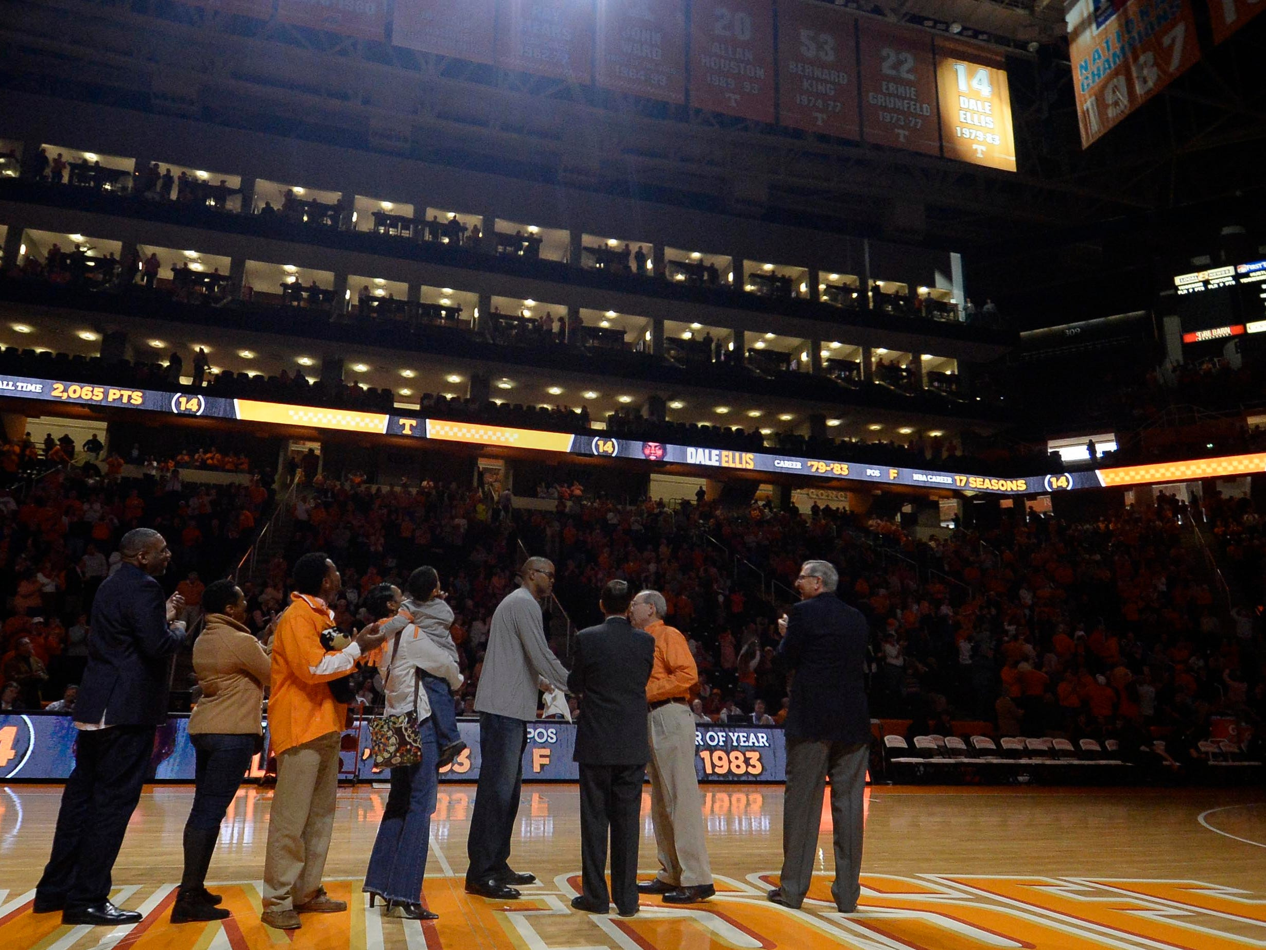 Former Tennessee basketball player Dale Ellis, center in grey, shakes hands with officials on court after having his #14 jersey retired in Thompson-Boling Arena before the Vols' game against Vanderbilt in Knoxville on Saturday, March 1, 2014.