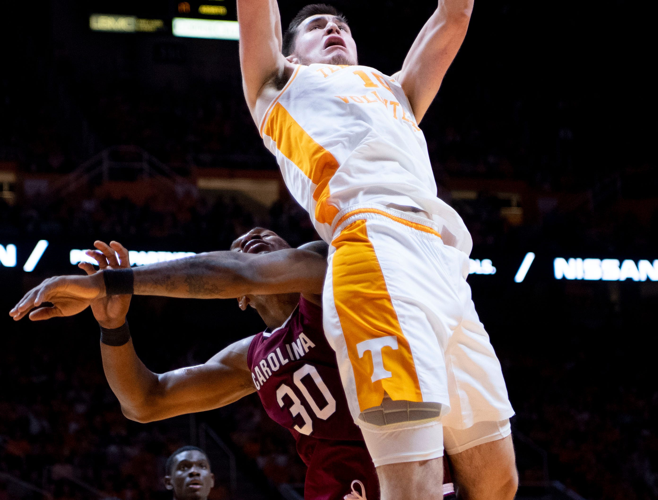 Tennessee's John Fulkerson (10) scores over South Carolina's Chris Silva (30) on Wednesday, February 13, 2019.