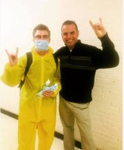 Brody Cox, a senior at Gibbs High School, wore a hazmat suit and mask to school on Thursday, Feb. 14, because of the flu going around in Knox County Schools. Cox stands with Dean Harned, right, a history teacher at Gibbs.