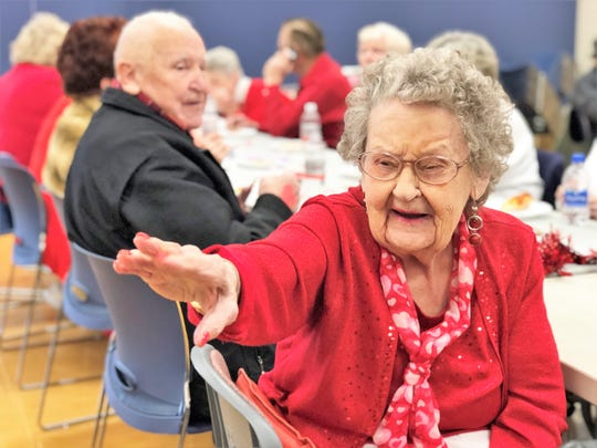 "Peggy Pate, 89, waves to a friend at The Heart of Halls event on Feb. 13. Pate said that she was not going to let a broken foot stop her from attending the Valentine's Day party. ""I really like the band and I love to jitterbug,"" she said."