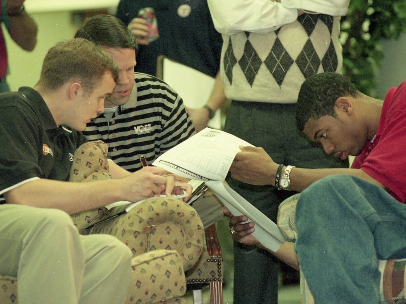 Aaron Greene and Associate Sports Information Director for basketball David Grimm look over one side of the NCAA tournament schedule as Rashard Lee looks over in March 1998.