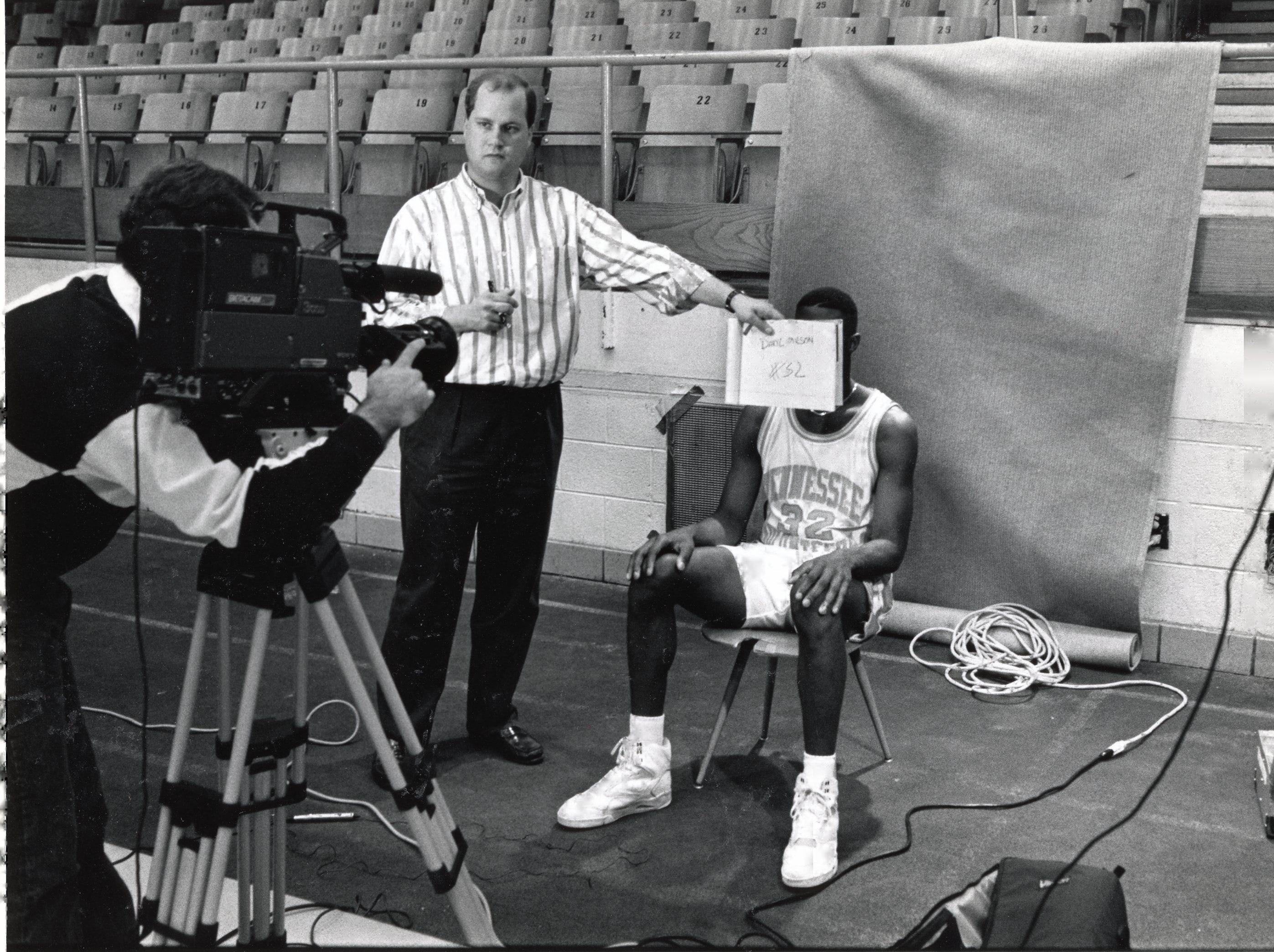 UT video services were on hand at the media day at Stokely to tape headshots of the Tennessee players for ESPN and others who may need video headshots of players in October 1990. Mike Moore is holding an identifying name and number in front of player Daryl Wilson for the taping.
