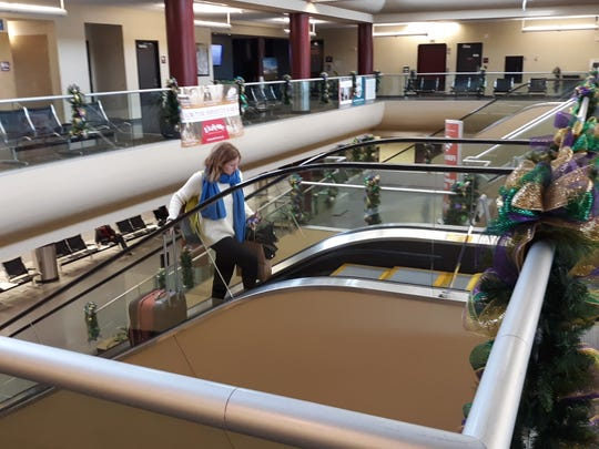 A traveler heads up the escalator at Lafayette Regional Airport. The state's fourth-largest airport is planning an $80 million renovation of its passenger terminal that will wrap up in late 2021.