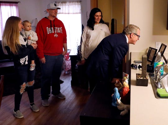 Gov. Mike DeWine, right, looks at family photographs as he visits the apartment of Allison, second from right, and Jess Springer and their daughters Brynn Springer, left, and Bryleigh Springer. DeWine visited the family as part of his tour of the Pearl House Wednesday, Feb. 13, 2019, in downtown Lancaster.