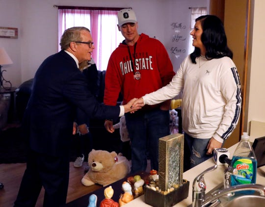 Gov. Mike DeWine, left, shakes hands with Allison Springer as he visits her family's apartment Tuesday, Feb. 13, 2019, at the Pearl House in downtown Lancaster. Center is Springer's husband Jess Springer.