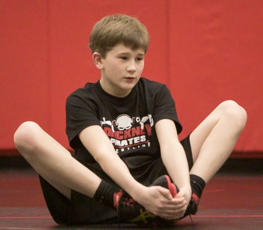 Pathfinder School eighth grader Levi Podhola stretches in preparation for a wrestling practice Wednesday, Feb. 13, 2019.