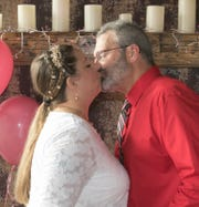April and Tim Ferrett kiss at the end of their wedding Thursday, Feb. 14, 2019, Valentine's Day, at downtown Howell's Uptown Coffee House.
