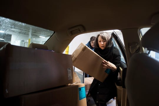 Toni Colagross of Delta Township, right, a volunteer with Helping Women Period, loads a car with boxes of tampons Wednesday, Feb. 13, 2019, at a storage unit in Lansing's Old Town that she and other volunteers will deliver throughout the community.  The organization has distributed about a million feminine hygiene products over the past four years.