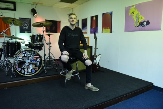 Ethan Ritenour sits on the stage that doubles as a rehearsal area inside DayTrip Studios.