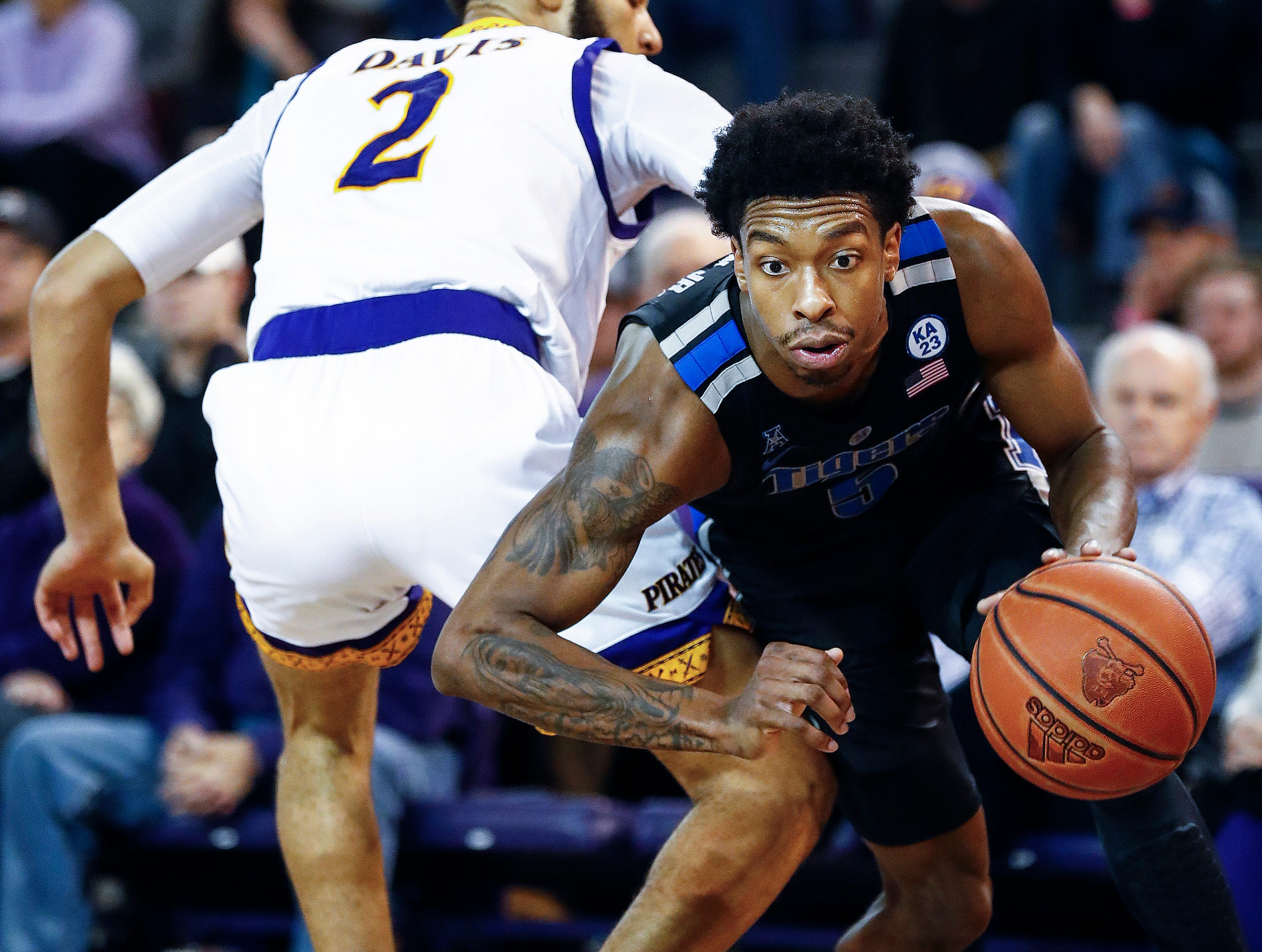 Memphis guard Kareem Brewton Jr. (right) drives by ECU defender K.J. Davis (left) for a layup during action in Greenville, N.C. Wednesday, February 13, 2019.