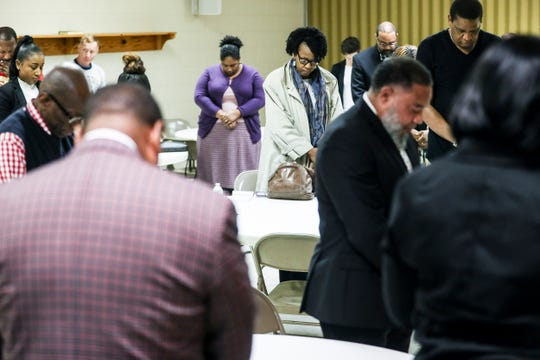 People bow their heads in prayer before the start of a Frayser Exchange meeting at Impact Church in Frayser on Feb. 14.