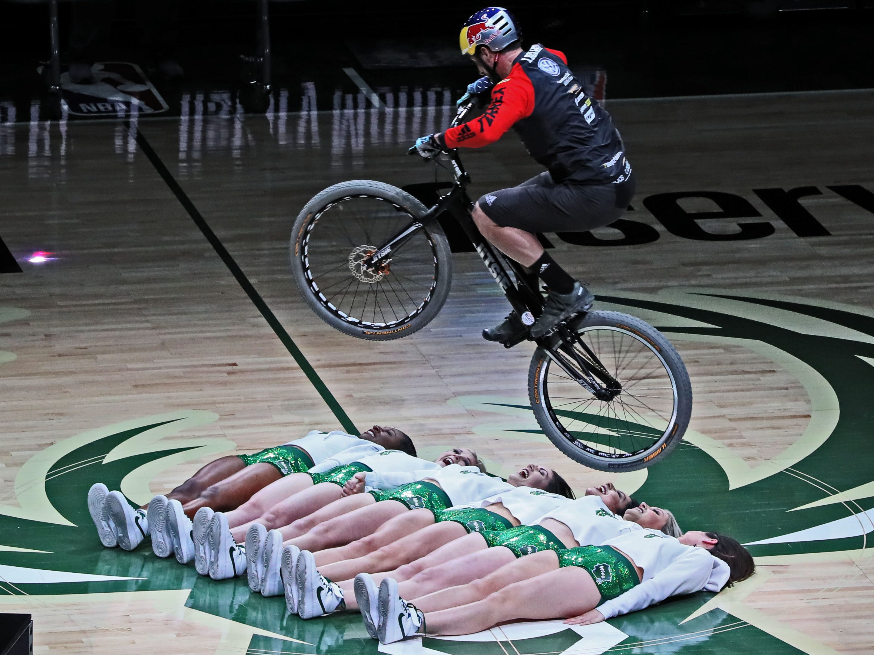 Kenny Belaey of Belgium, a champion mountain bike trials rider, using no ramp, jumps over six of the Milwaukee Bucks Dancers during the halftime show on Feb. 6.