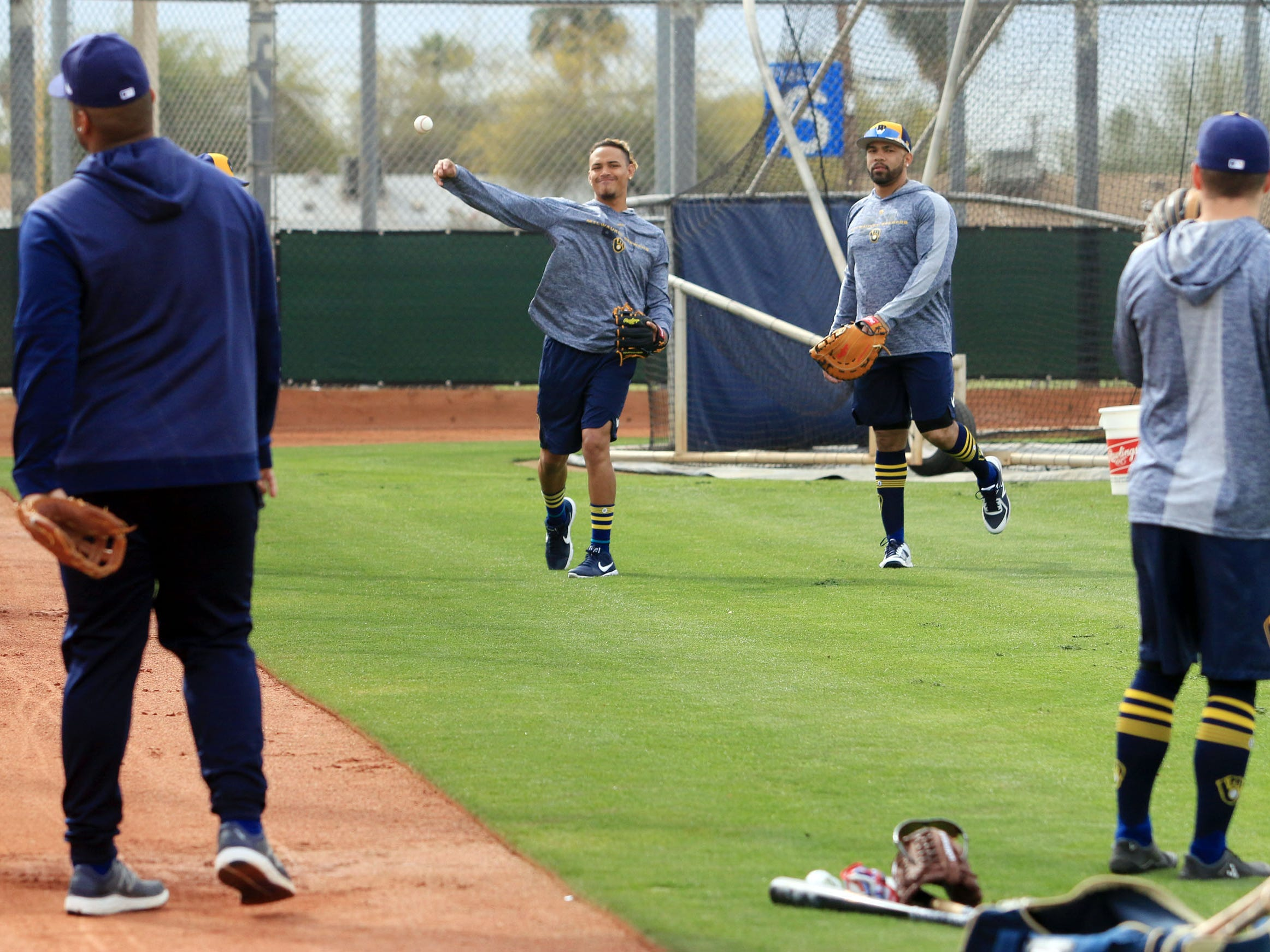 Position players who attended the first day of the Brewers' spring training workouts warm up their arms by playing play catch before practice began in earnest on Wednesday in Phoenix.