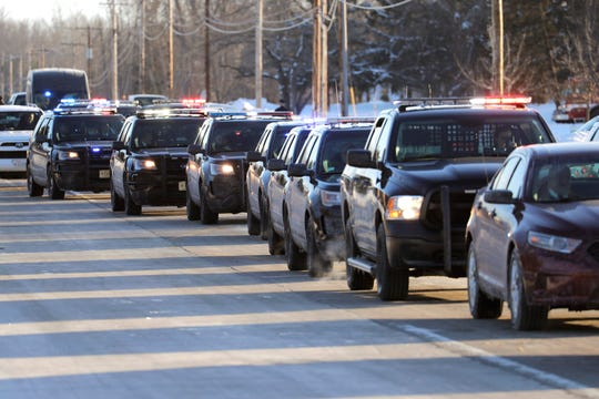 Police, fire and first responder vehicles  drives under a large American flag after funeral services at Oak Creek Assembly of God Church. After the funeral a large procession of vehicles drove under a large American flag at patrons showed their respects after the funeral for slain Milwaukee Police Officer Matthew Rittner.