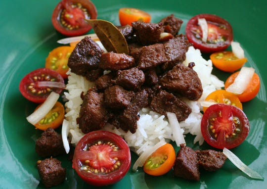 Pork adobo, a traditional Filipino entree, is served over a mango, tomato apple salad.