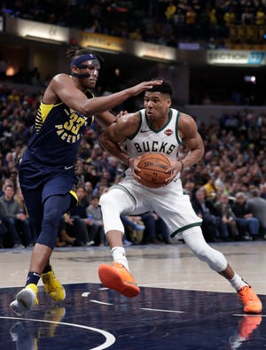 Bucks forward Giannis Antetokounmpo takes it to the race while being guarded Pacers center Myles Turner during the second half  Wednesday.