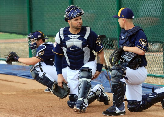 Brewers catcher Manny Pina talks with non-roster invitee Tuffy Gosewisch (right) as non-roster invitee Payton Henry catches a pitch in the bullpen Thursday. Pina has been designated as the No. 2 catcher.