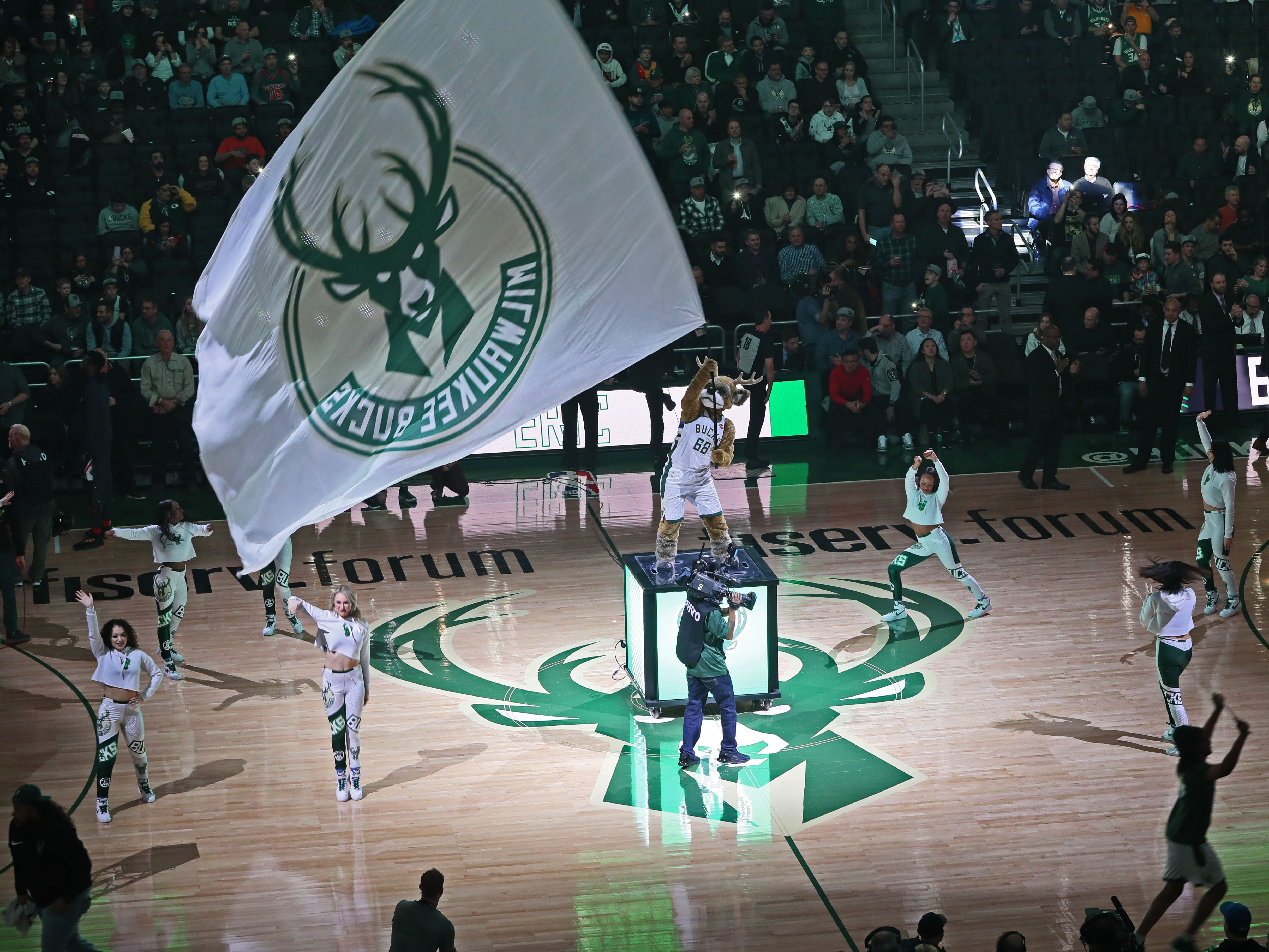 Bango waves a flag as members of the Milwaukee Bucks Dancers perform while the players are introduced Feb. 6.