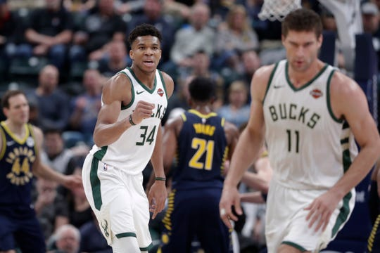 Bucks forward Giannis Antetokounmpo  celebrates after an assist on a shot by center Brook Lopez.