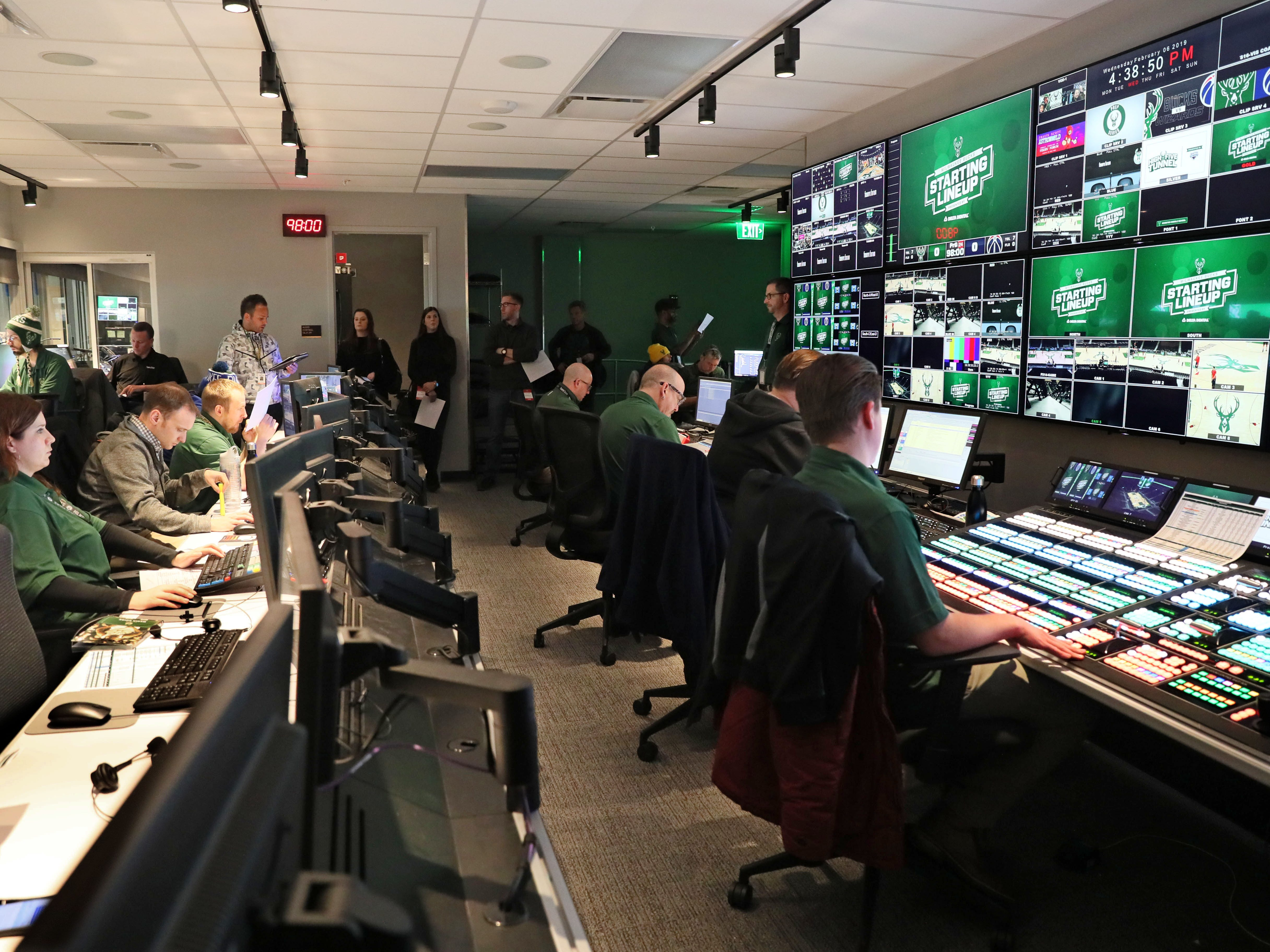 Johnny Watson (rear center in white), the Milwaukee Bucks executive in charge of all in-arena activities during games, meets with the control room staff before the game starts to run through the list of entertainment activities.