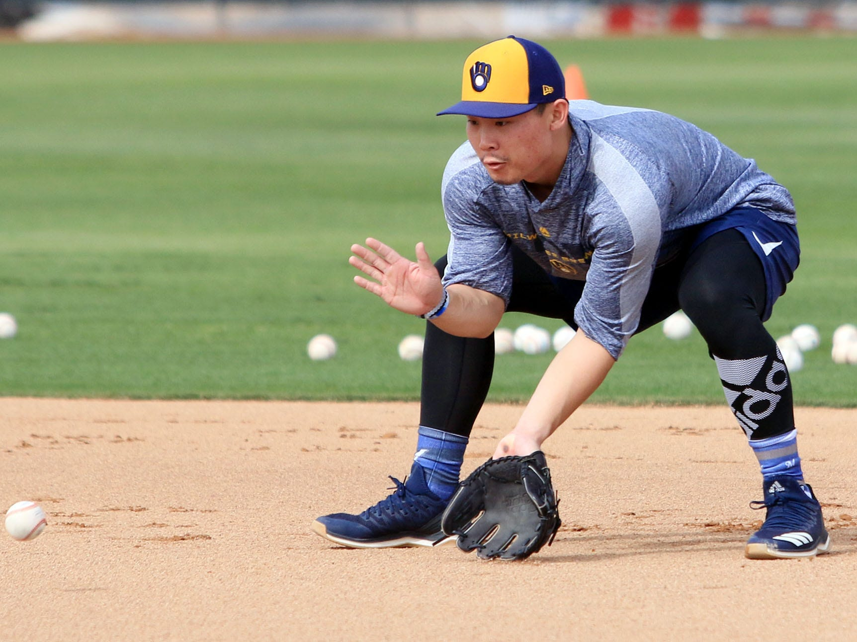 Brewers top-prospect Keston Hiura fields grounders during the first day of spring training practices on Wednesday.