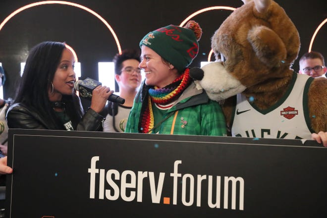 In this 2019 file photo, Bucks in-game host Melanie Ricks, left, interviews the Fiserv Forum's millionth fan, Samantha Holschuh while mascot Bango looks on.