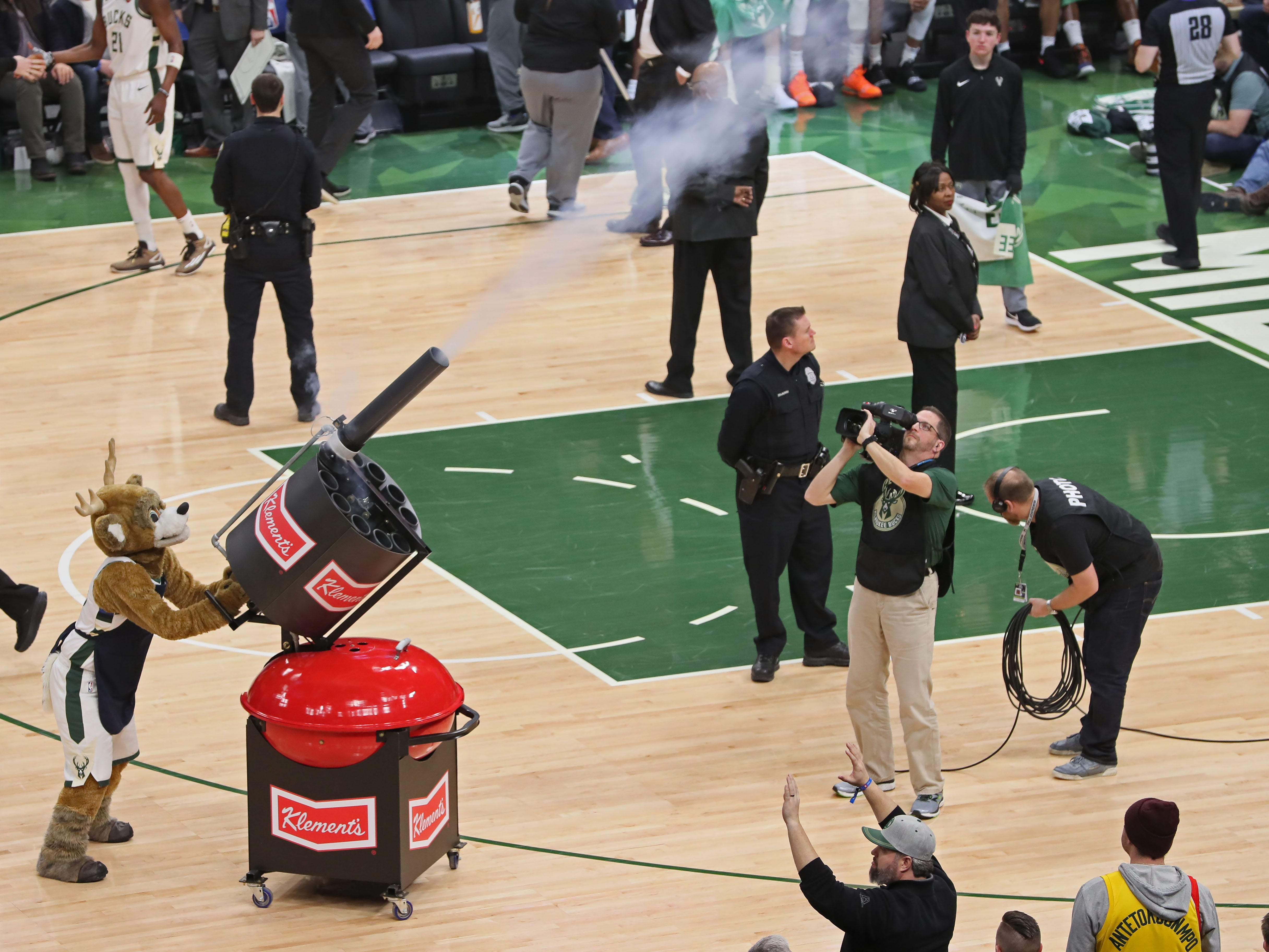Bango launches T-shirts into the crowd during a timeout in the game between the Bucks and Wizards.