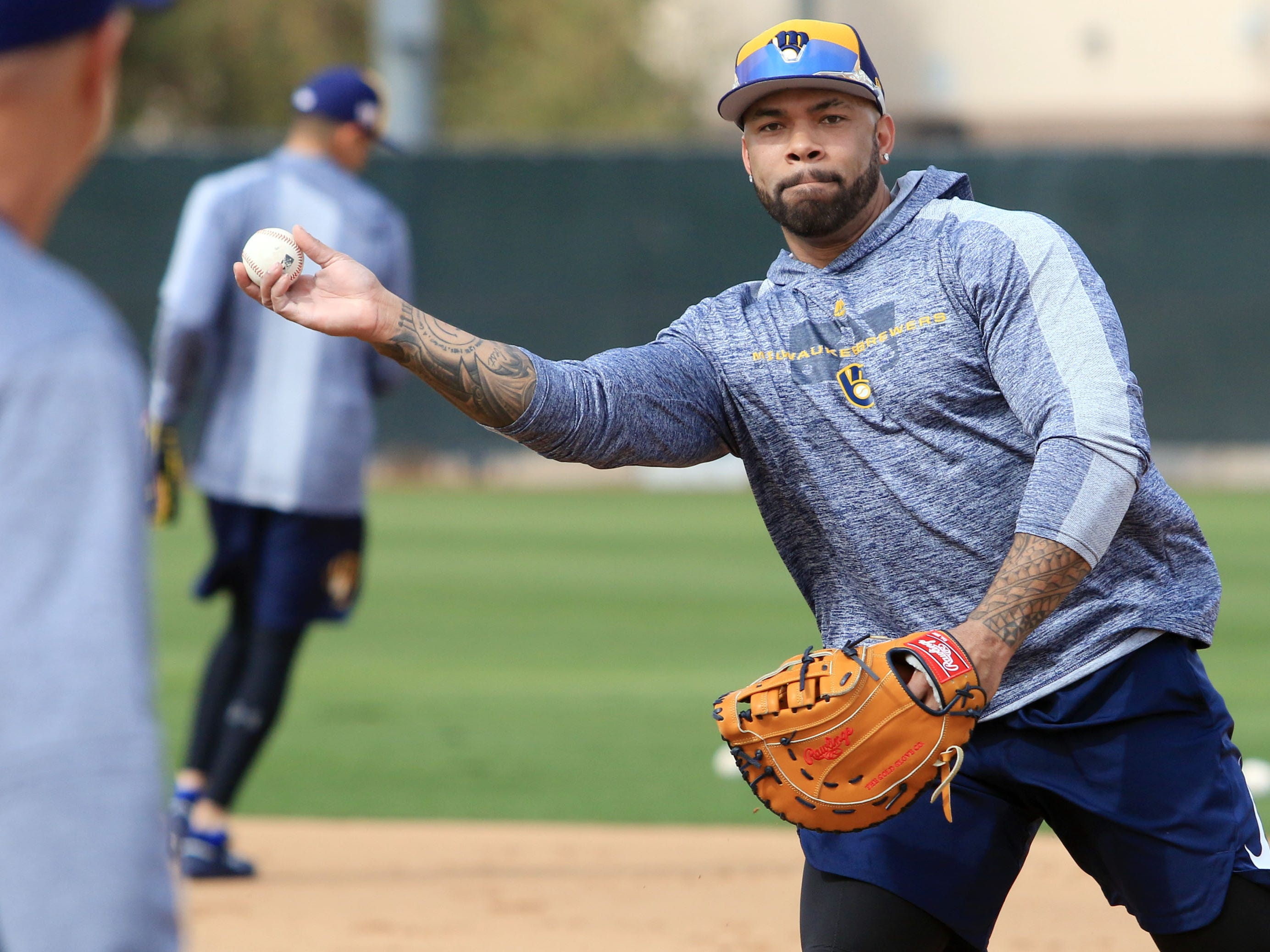 Brewers first baseman Eric Thames throws to a pitcher covering first during drills on the first day of spring training workouts in Phoenix.